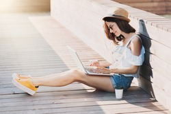 Young adult using laptop outdoors