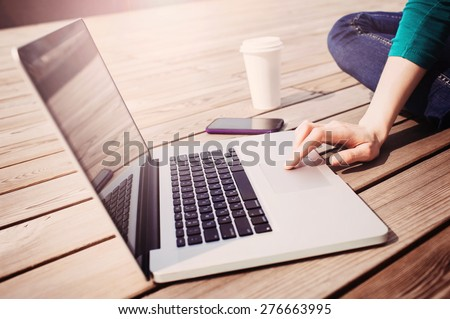 Young adult using laptop outdoors stock photo