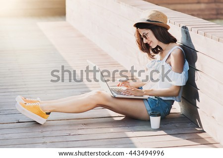 Young adult using laptop outdoors #443494996