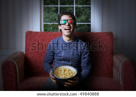 Young adult watching a 3d movie at home