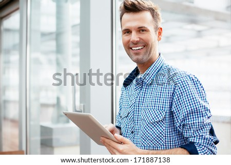 Young adult with a tablet in his hand and smiling into the camera