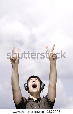 young adult with headphones (focus point on face) - stock photo