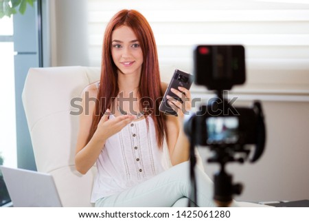 Young adult woman blogging about newest mobil phone