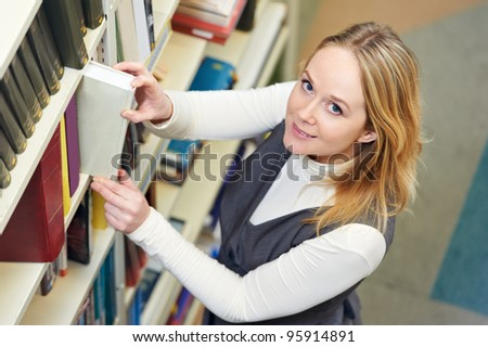 young adult woman college student in a library selecting books from bookshelf during self education