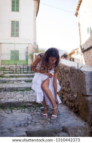 Young adult woman fixing her shoe as she walks down cobbled steps.