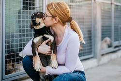 Young adult woman holding adorable dog in animal shelter.