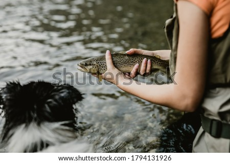 Young adult woman is fishing alone on fast mountain river. The girl holds a live trout before releasing it into the river again.