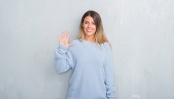 Young adult woman over grey grunge wall wearing winter outfit showing and pointing up with fingers number five while smiling confident and happy.