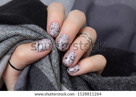 Young adult woman's hands with pink nude fashionable nails on gray concrete background. Winter autumn nail design. Manicure, pedicure beauty salon concept.