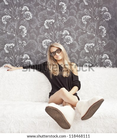 young adult woman sitting on a white couch in her slippers wool white