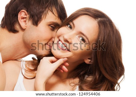Young adult woman smiling and holding hand near mouse with boyfriend kissing her