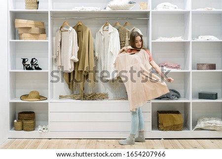 Young adult woman standing near modern wardrobe at home with contemporary interior, choosing trendy clothes, having difficult choice not knowing what to put on, trying on fashionable wear Foto stock ©