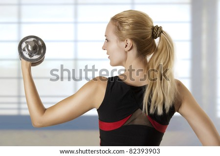 Young adult woman workout with dumbbell on fitness