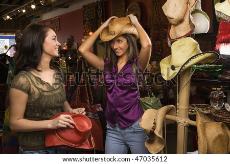 Young adult women trying on cowboys hats in a retail store. Horizontal shot.