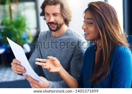 Young adults coworkers analyzing document