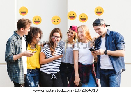 Young adults enjoying together outdoors with their smartphones