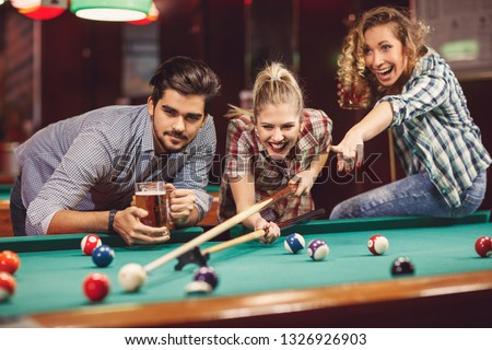 Young adults friends in bar playing billiard together