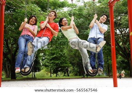 Young adults in playground, standing on swings