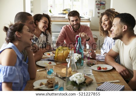 Young adults laughing as they talk at a table over lunch #521227855