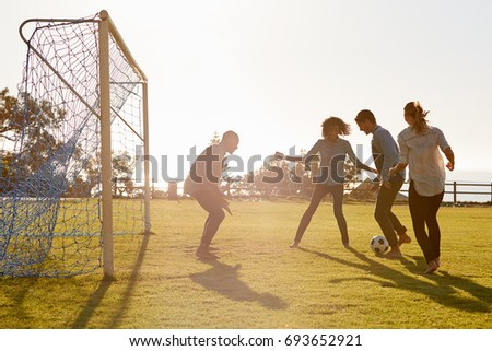 Young adults playing football in park one in goal, side view - Shutterstock ID 693652921