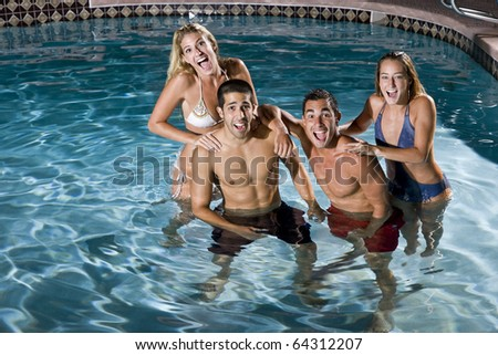Young adults (20s) having fun in swimming pool at night