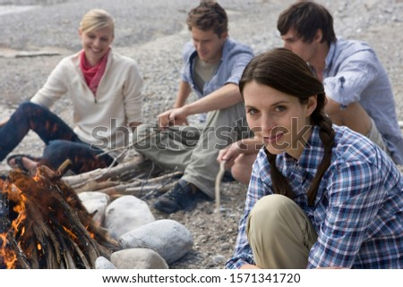 Young adults sitting around campfire