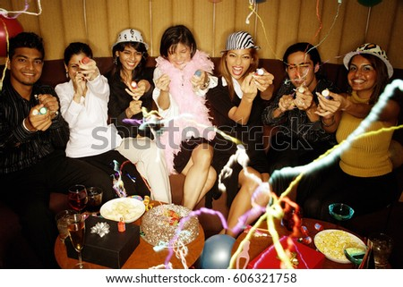Young adults sitting side by side, celebrating, playing with streamers