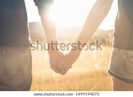 Young affectionate couple holding hands walking outdoors at sunset.