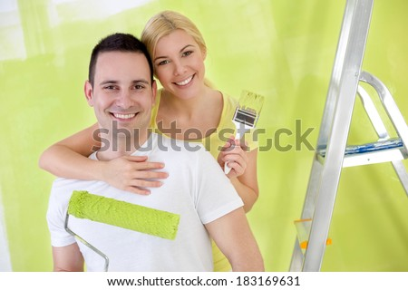 Young affectionate,  happy handy couple painting new house