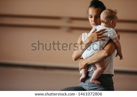 Young affectionate mother embracing her baby boy while having sports training in a health club. Copy space.