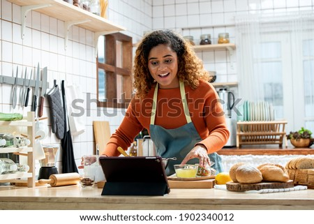 Young Afican American woman learning online  cooking class via tablet computer in kitchen at home Photo stock ©