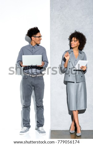 Young african amercian businessman with laptop and businesswoman with tablet in hands looking at each other on grey and white background  #779056174
