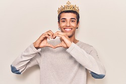 Young african amercian man wearing prince crown smiling in love showing heart symbol and shape with hands. romantic concept.