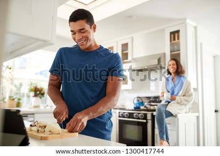 Young African American adult man standing in the kitchen preparing food, his partner sitting on kitchen worktop behind him, focus on foreground