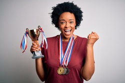 Young African American afro athlete woman with curly hair wearing medals holding trophy screaming proud and celebrating victory and success very excited, cheering emotion