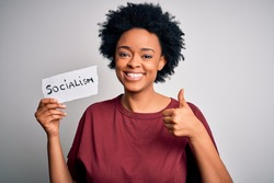 Young African American afro politician woman with curly hair socialist party member happy with big smile doing ok sign, thumb up with fingers, excellent sign