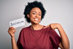 Young African American afro politician woman with curly hair socialist party member with surprise face pointing finger to himself