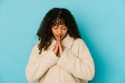 Young african american afro woman isolated praying, showing devotion, religious person looking for divine inspiration.