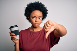 Young African American afro woman with curly hair drinking cup of coffee with angry face, negative sign showing dislike with thumbs down, rejection concept