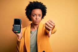 Young African American afro woman with curly hair holding dataphone payment device with angry face, negative sign showing dislike with thumbs down, rejection concept
