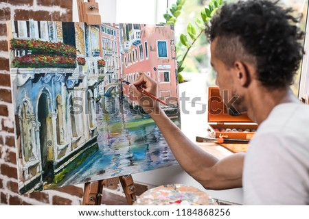 Young African-American artist painting picture in workshop #1184868256