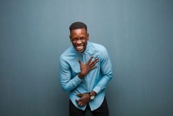 young african american black man laughing out loud at some hilarious joke, feeling happy and cheerful, having fun against grunge wall