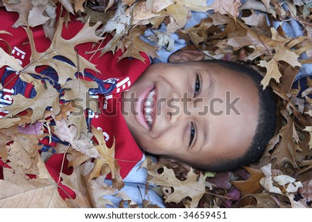 Young African-American boy in seasonal Fall leaves