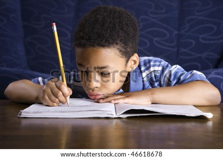 Young African American boy sitting on the floor in front of a coffee table doing homework. Horizontal shot.