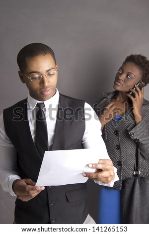 Young African American Business Couple busy with a contract talking on a Cellphone