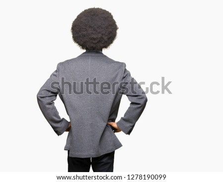 Young african american business man with afro hair wearing glasses standing backwards looking away with arms on body