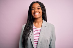 Young african american business woman standing over pink isolated background with a happy and cool smile on face. Lucky person.