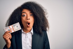 Young african american business woman with afro hair holding a bunch of cash dollars banknotes scared in shock with a surprise face, afraid and excited with fear expression