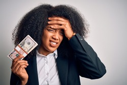 Young african american business woman with afro hair holding a bunch of cash dollars banknotes stressed with hand on head, shocked with shame and surprise face, angry and frustrated. Fear and upset