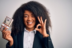 Young african american business woman with afro hair holding a bunch of cash dollars banknotes doing ok sign with fingers, excellent symbol